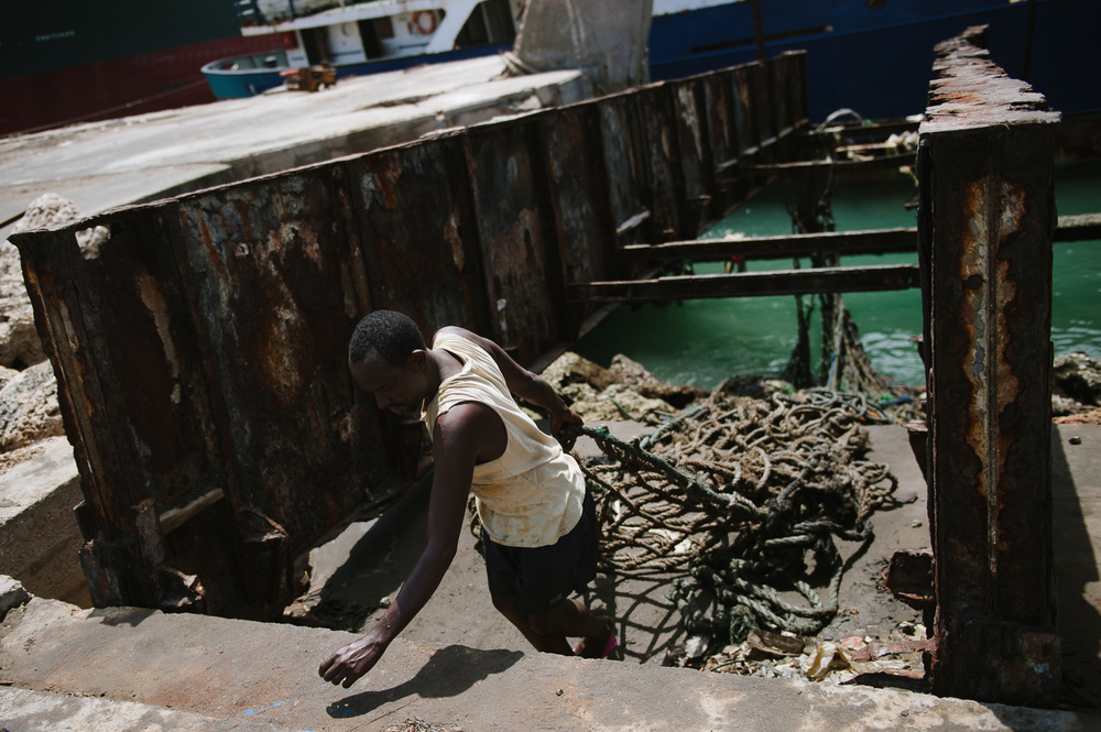 A man hauls a cargo net from a transporter boat in the port