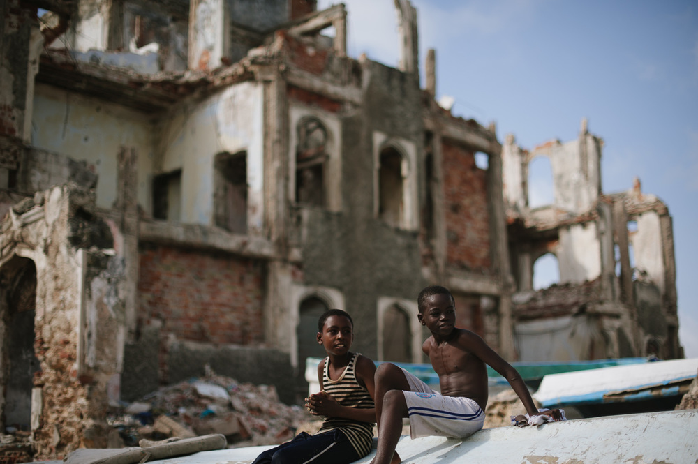 Boys sit on a skiff amidst the ruins of harbour buildings destroyed during Somalia's two-decade long civil war.