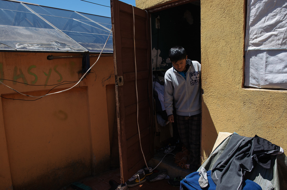 """Ruben Flores (13) steps out of the small room his family inhabits in the """"New Day Foundation"""" association in La Paz, Bolivia. Ruben is a shoe-shiner and helps support his family through the wages he earns."""