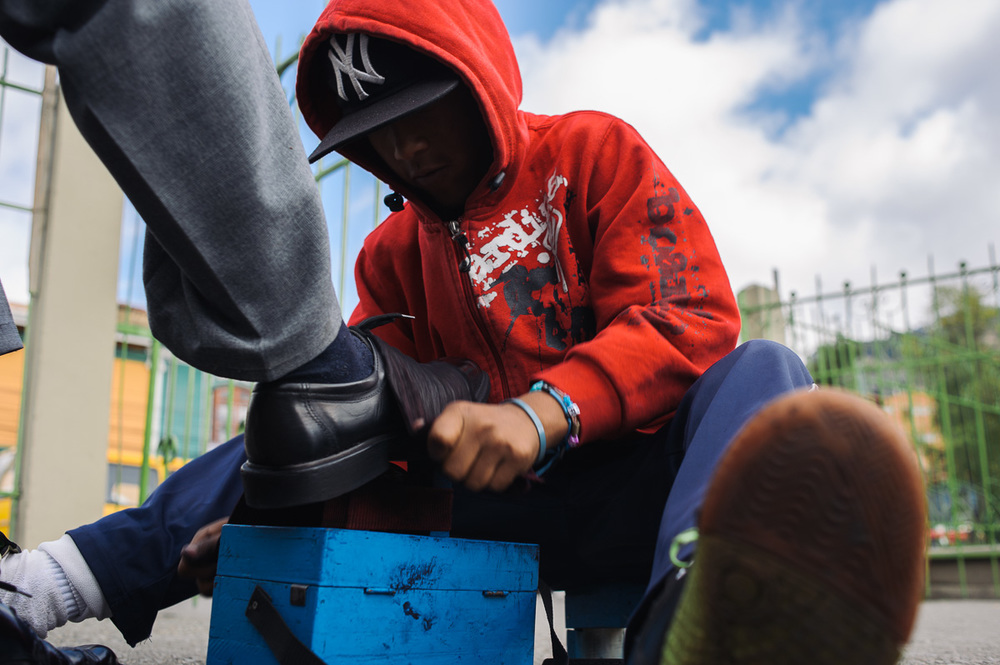Ruben Flores (13) shines the shoe of a man in the street of central La Paz, Bolivia.