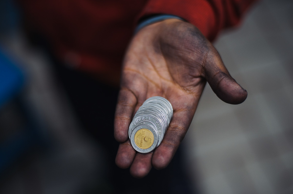 Ruben Flores (13) holds the money he earned from a day's shoe-shining, 26 Bolivianos, just under $4 (USD), pictured at his home in La Paz, Bolivia.