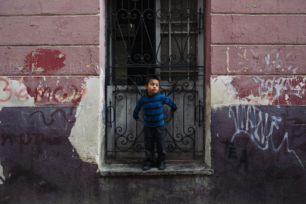 """Jonny, Ruben's five year old brother, stands in a window of the """"New Day Foundation"""" as his brother plays football in the street in La Paz, Bolivia."""