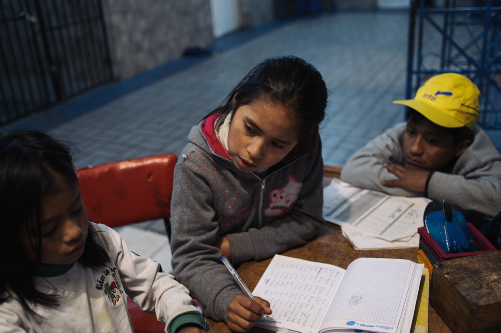 """Edith Flores (10, centre) helps her sister, Rayna (7) with homework as Ruben watches in the """"New Day Foundation"""", a centre for shoe-shiners where the family lives, in La Paz, Bolivia."""