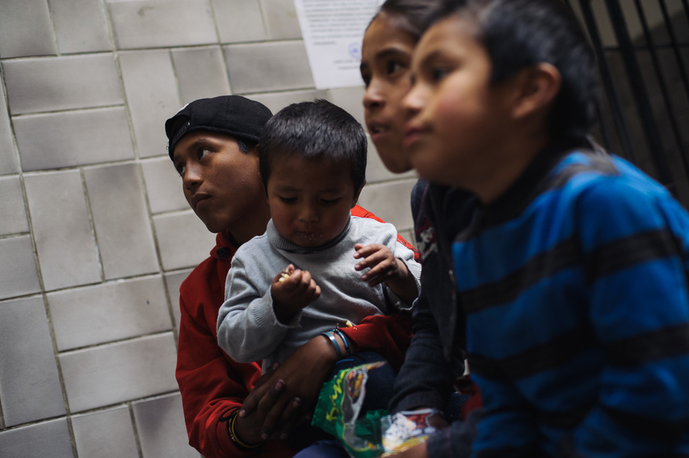 """Ruben Flores (13) sits with his younger siblings as they watch television in the """"New Day Foundation"""" centre where the family lives in La Paz, Bolivia. Ruben works as a shoe-shiner, and his income helps to provide for the family when times are tough."""