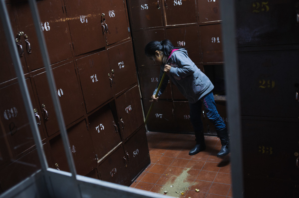 """Edith Flores (10) sweeps the floor of the locker-room in the """"New Day Foundation"""", a centre for shoe-shiners in La Paz, Bolivia. Edith's brother, Ruben (13), and her father, Jonny, both work as shoe-shiners -- a highly stigmatised. Edith does not formally work for pay, but regularly helps her mother clean the centre, where she is care-taker and the family live."""