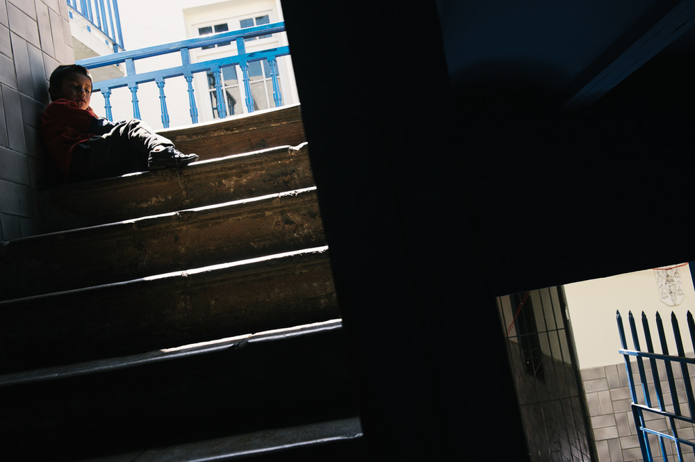 """Jonny, Ruben's five year old brother, sits on a staircase in the """"New Day Foundation"""", a centre for shoe-shiners where he lives with his family in La Paz, Bolivia."""