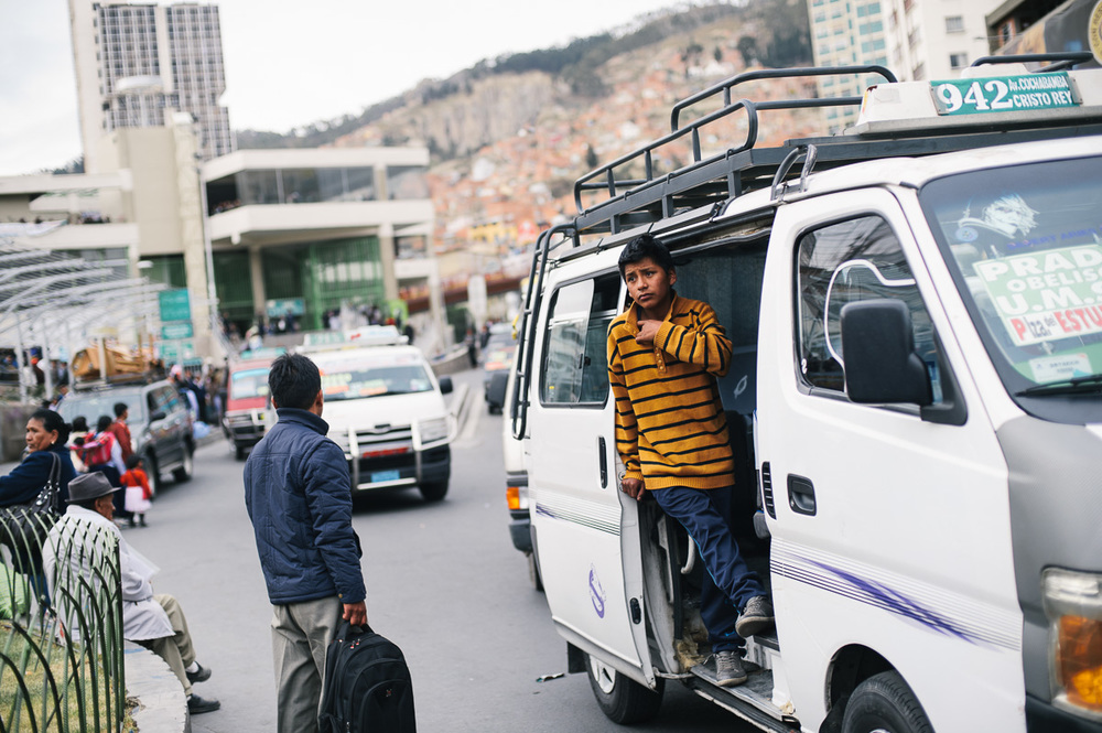 """A young boy works as a """"vocedore"""", touting for minibus passengers at a bus-stop in La Paz, Bolivia. As well as calling the bus route to passengers and potential clients, the vocedores open and close the minibus door, a job deemed """"hard labour"""" and forbidden for young children."""