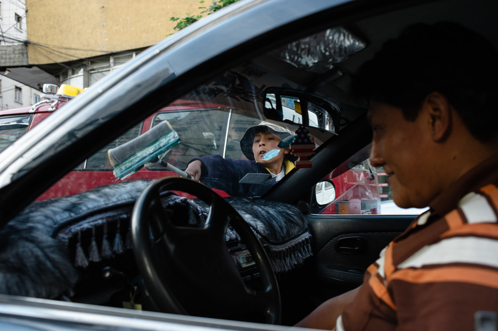 Albero, 9, cleans a car window in a queue of traffic at a traffic-light on a major road in La Paz, Bolivia. Albero earns 1 boliviano ($0.14 USD) per car window he cleans. Despite working under the legal age, police officers regularly passing him by never pulled him up for working.