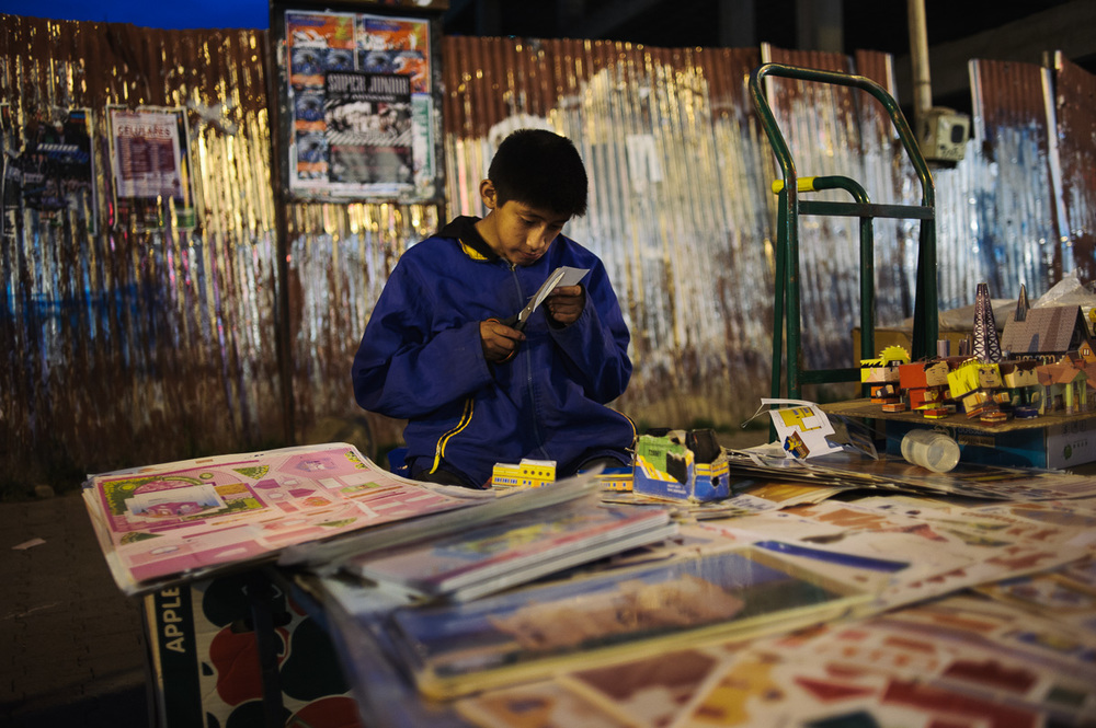 Brandon (13) works on his family's stall in a street market in La Paz, Bolivia. He has been working since he was 7.