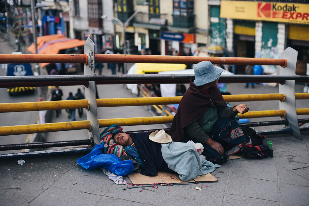 A child sleeps as his mother begs on a pedestrian bridge in central La Paz, Bolivia.