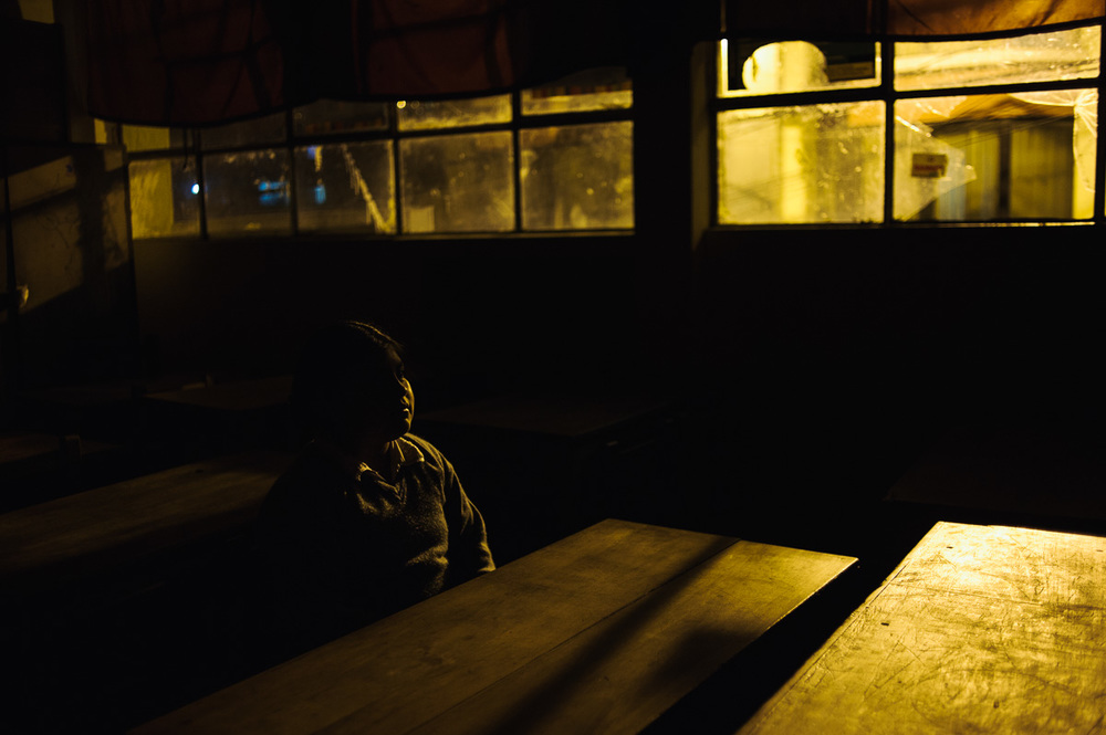 Betsabel (8) poses for a picture in her classroom after a night-school class with her father in La Paz, the Bolivian capital.  Betsabel works for her godparents as domestic help, earning her keep from them, despite being two years too young to legally work under Bolivia's child labour laws.
