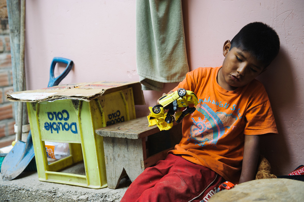"Brandon, 9, plays with a toy car at the house of his ""godfather"", the coca plantation owner for whom he works, in the village of Coripata in the ""Los Yungas"" region of Bolivia."