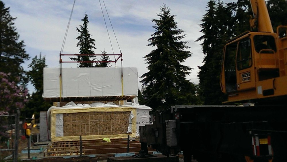 As the boxes come along a separate crew follows up and places batt insulation, shown here in yellow, the insulationacts as a fire/smoke separation between units. Additionally, crews mechanically attach straps which structurally tie the modules to the foundation and to each other.