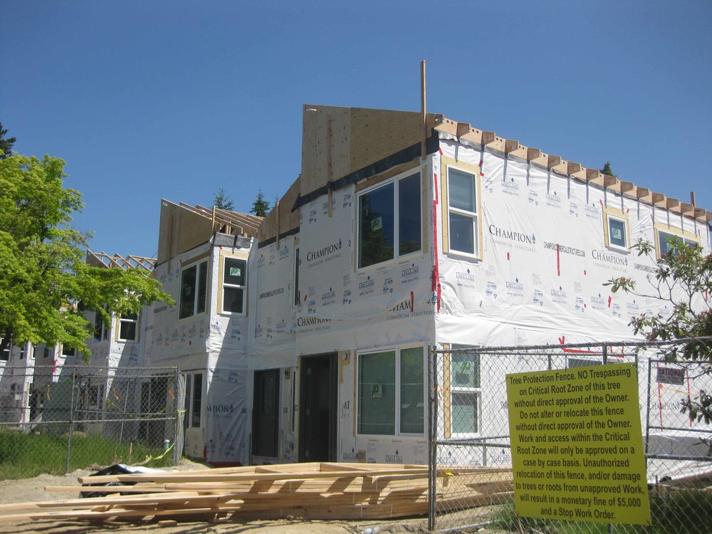Once the boxes have been set, the construction takes on a more typical construction process. The air barrier is seamed together at all gaps between modules, all while the roof trusses are set atop the second floor modules.  Once the trusses are in place, the roof is sheathed, papered, and shingled.