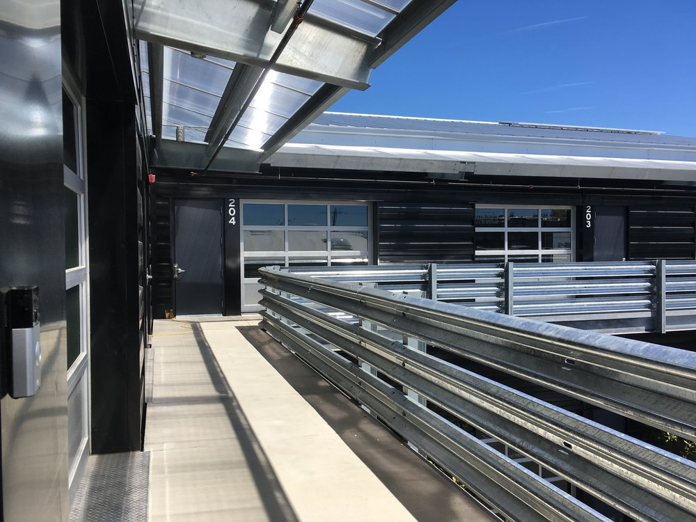 View north along upper balcony walkway. The owner sourced the guardrails in front of roll-up doors, portions in front of the garage doors are removable for fork-lift deliveries from the parking lot below.