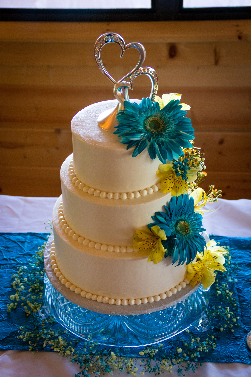 Three tier all-white cake.  Flowers are not included, but may be added.  Please call for quote.