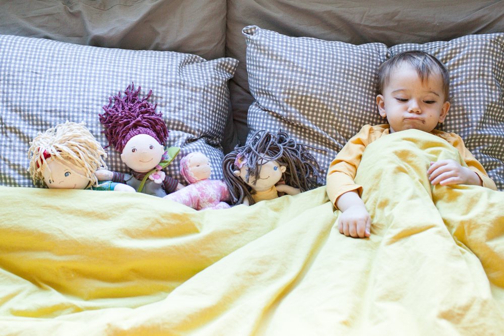 A portrait of Naomi, once a week, every week, in 2014  - she loves to play in the guest room's bed, putting all her little friends to nap. -