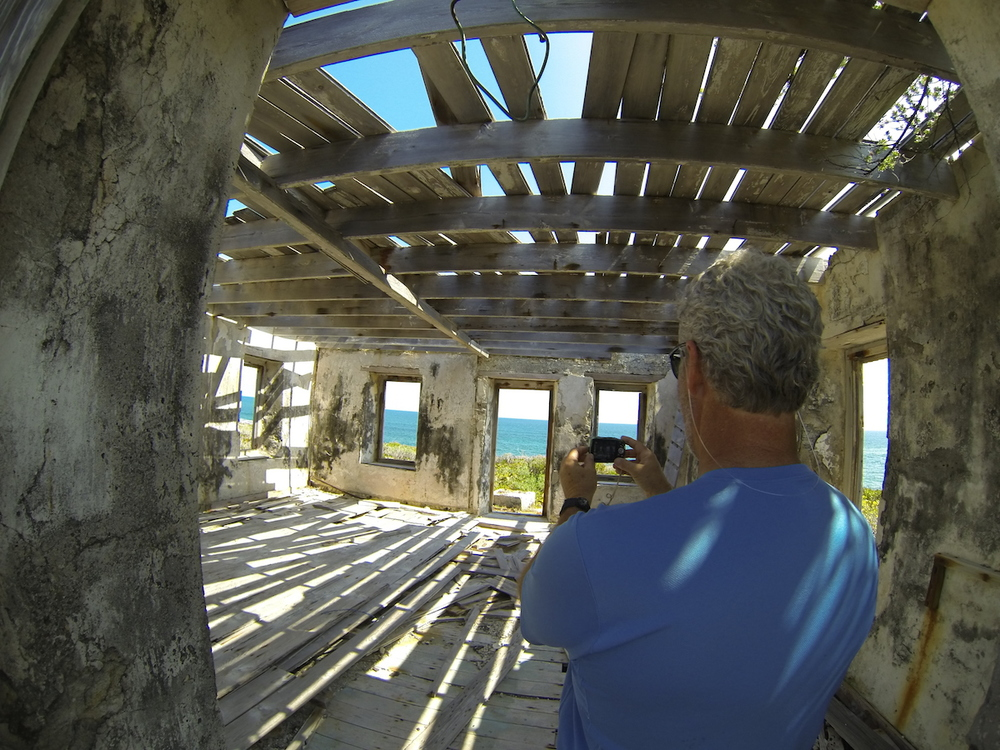 Inside the old abandoned lighthouse (that's Tom). The reef break is visible through the windows on the left.