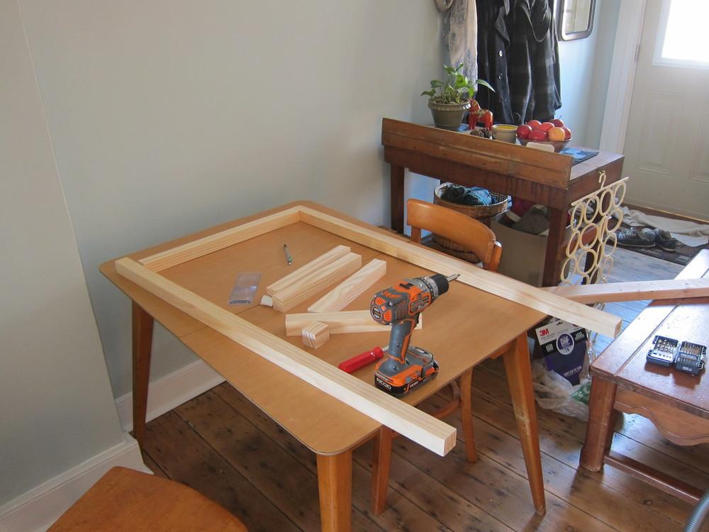 Då vårt golv inte är rakt använde jag köksbordet för att få en platt yta att få ihop ramen