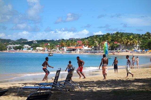 Kids spelar fotboll på stranden