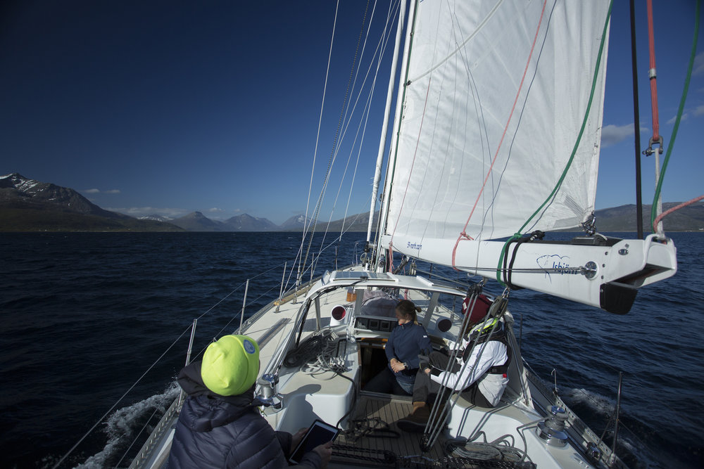 Motorsailing through the Tjeldsundet, with snow-capped mountains providing the scenery.