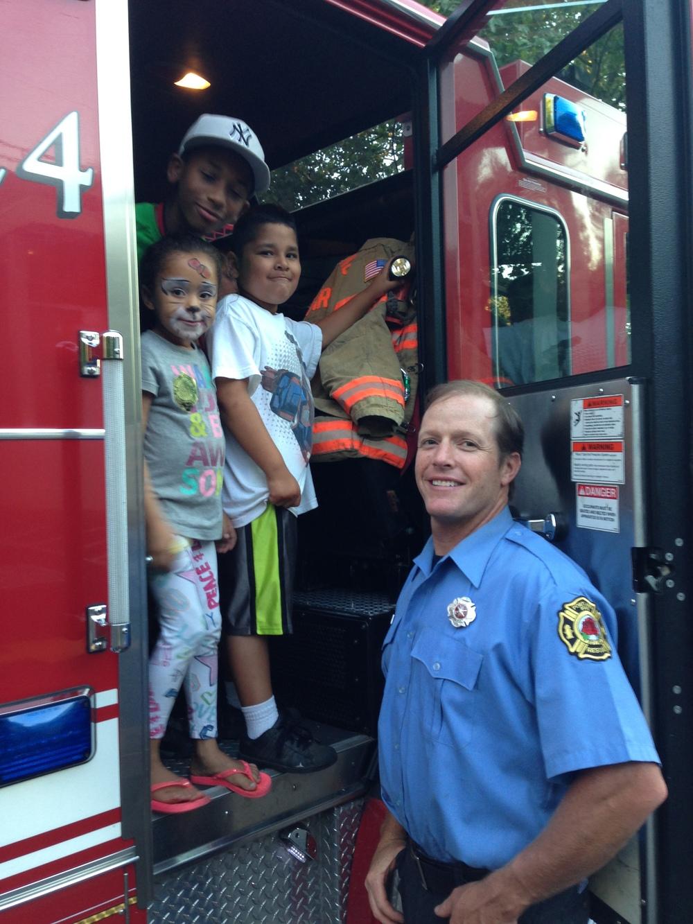 Firemen let kids play in their firetrucks