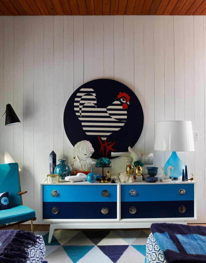 A CIRCULAR VINTAGE FRENCH ARTWORK HANGS IN A CHARACTERFUL GUEST BEDROOM IN THE SHELTER ISLAND APARTMENT, WHICH ALSO FEATURES FURNITURE, RUG AND IMPRESSIVE BIBELOTS BY JONATHAN ADLER.PHOTOGRAPH © RICHARD POWERS