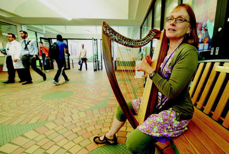 Bev Ross, a member of the Artists on the Wards program at the U of A Hospital, plays her harp in the hospital    Photo Credit: John Lucas/Edmonton Journal