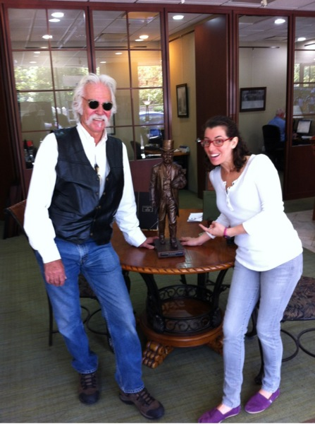 Renowned sculpture Dennis Downes and Lauren Singer from Chicago Crime Tours posing with miniature statute of Cap Streeter.