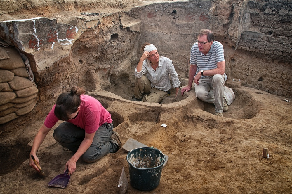 Burcu Tung and Ian Hodder discuss excavation plans in Building 77 (North Area) during the last days of the 2013 season. In the foreground, Renata Araujo cleans her area for a photo.