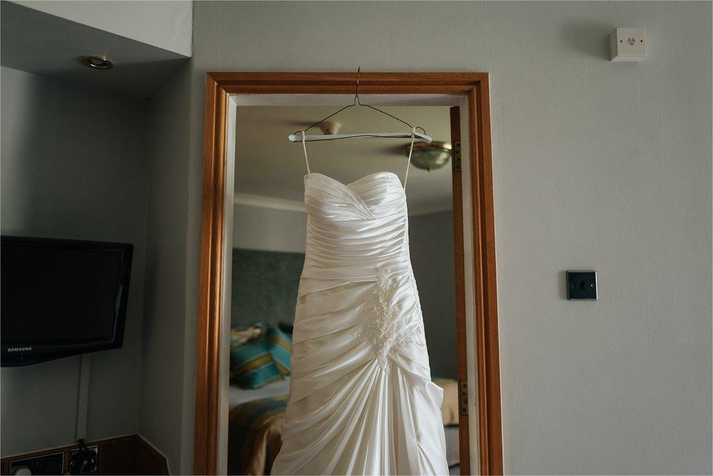 wedding dress hanging in door way