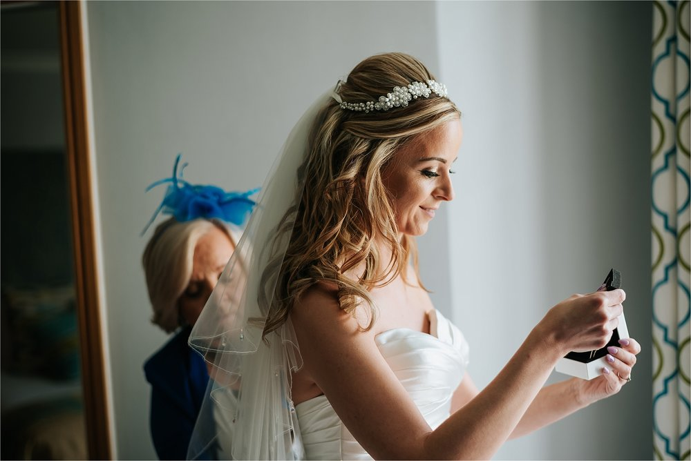 bride putting jewellery on before wedding
