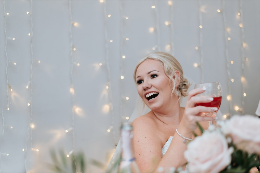 bride laughing at wedding speeches