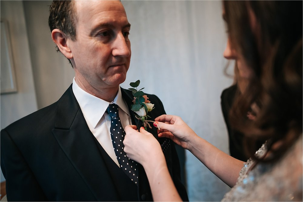 bridesmaid putting a flower on to dad at wedding