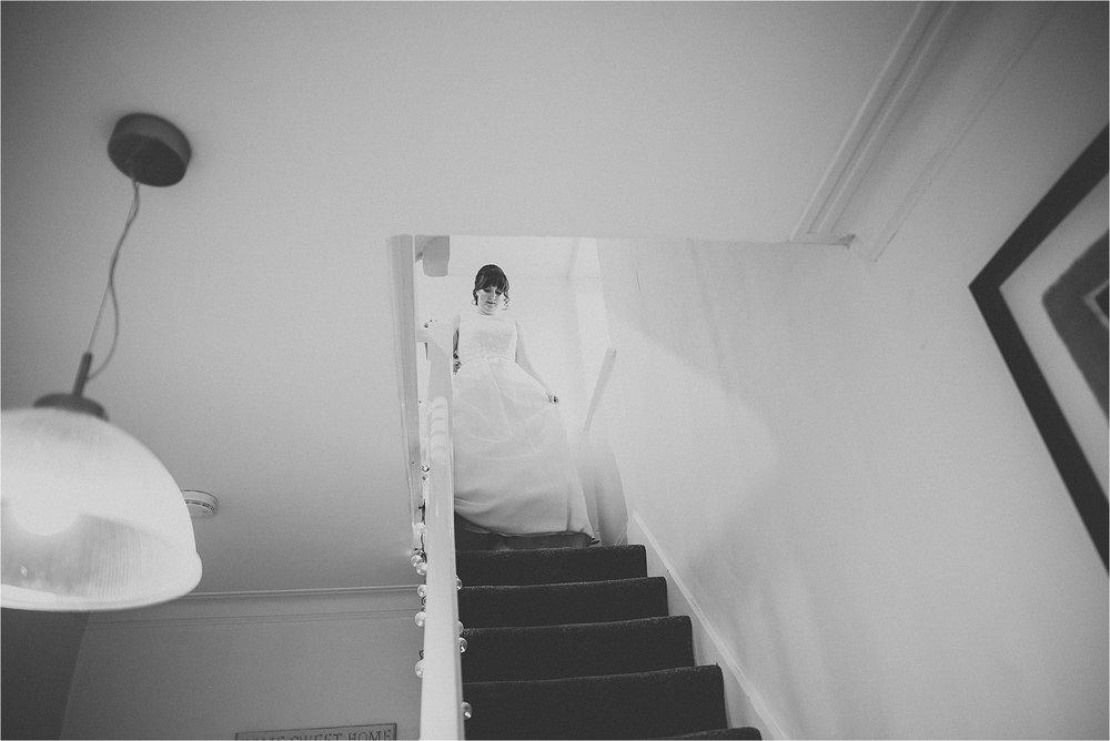 bride walks down stairs in charlotte balbier gown