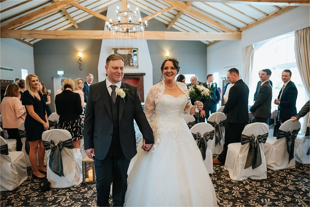newly married couple walk out of ceremony room