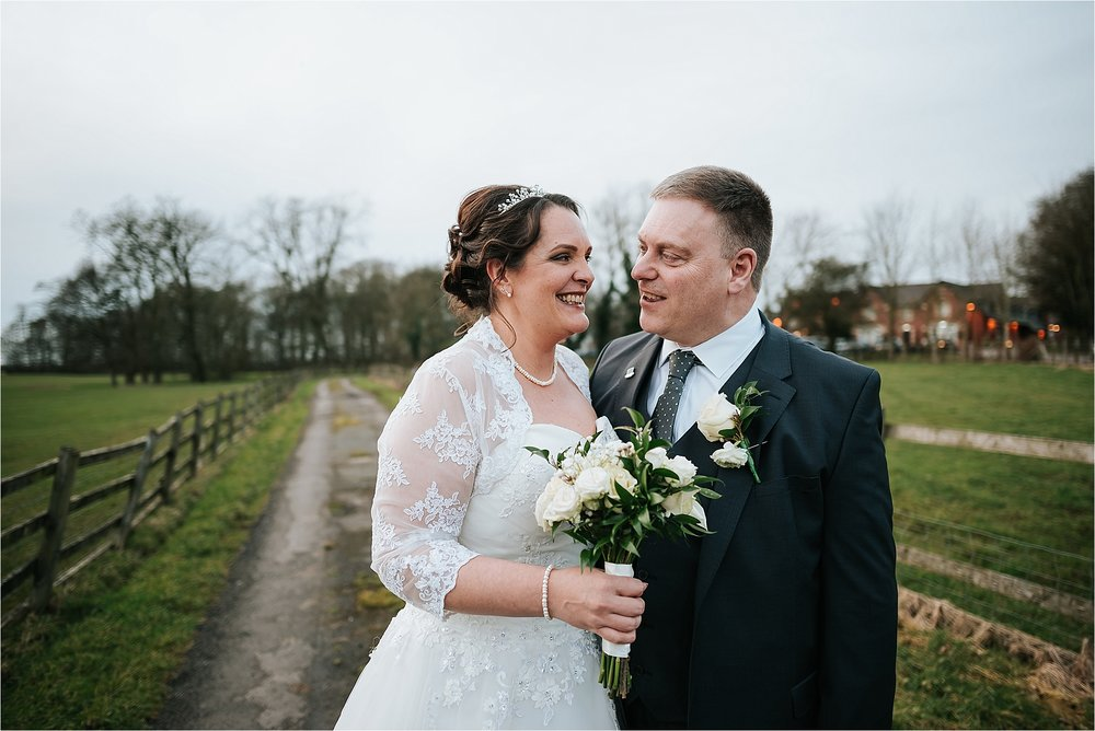 bride and groom in field outside the villa wrea green