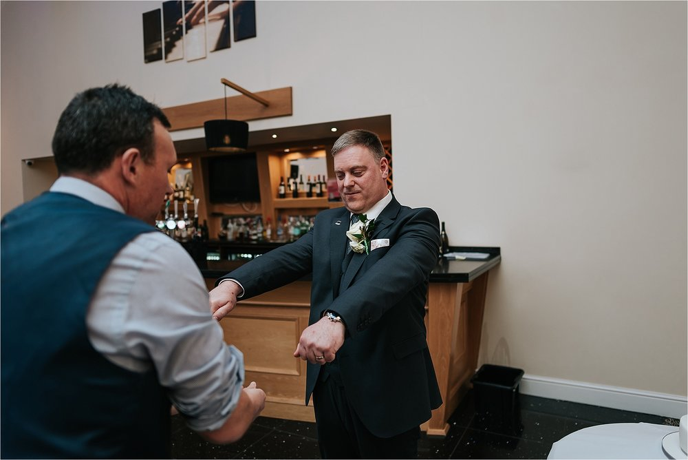 magician entertains groom at a wedding