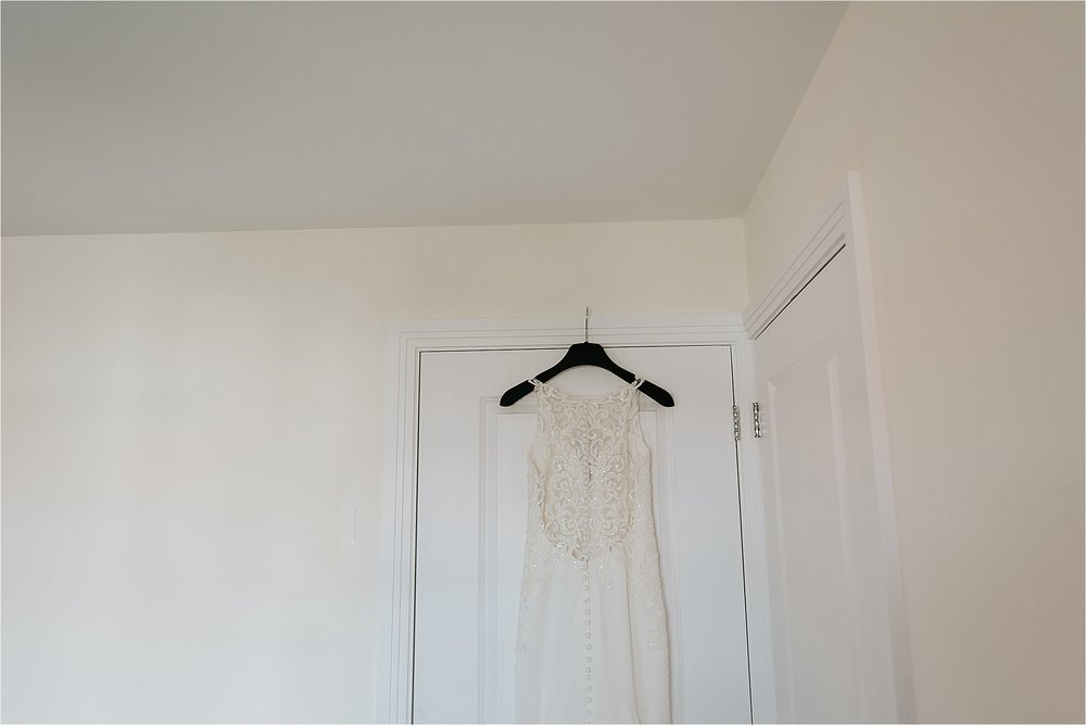 wedding dress hung on door
