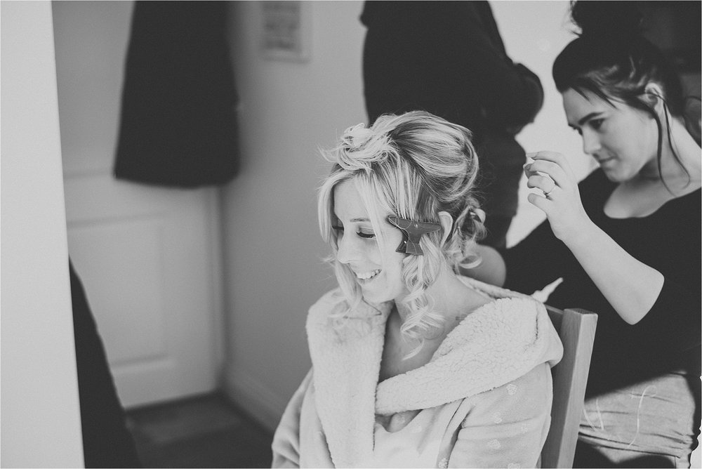 bride getting hair and makeup done before wedding