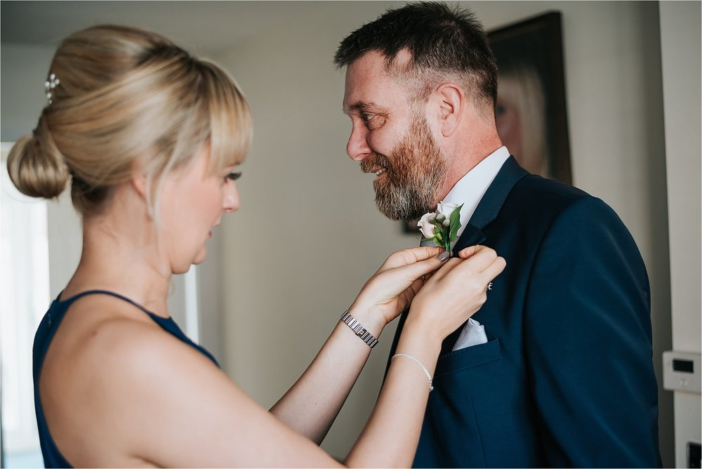 bridesmaid helps dad put his buttonhole on