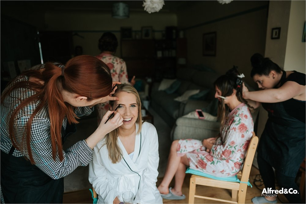 bride getting her make up on before wedding