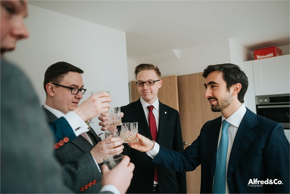 groomsmen doing cheers with whiskey