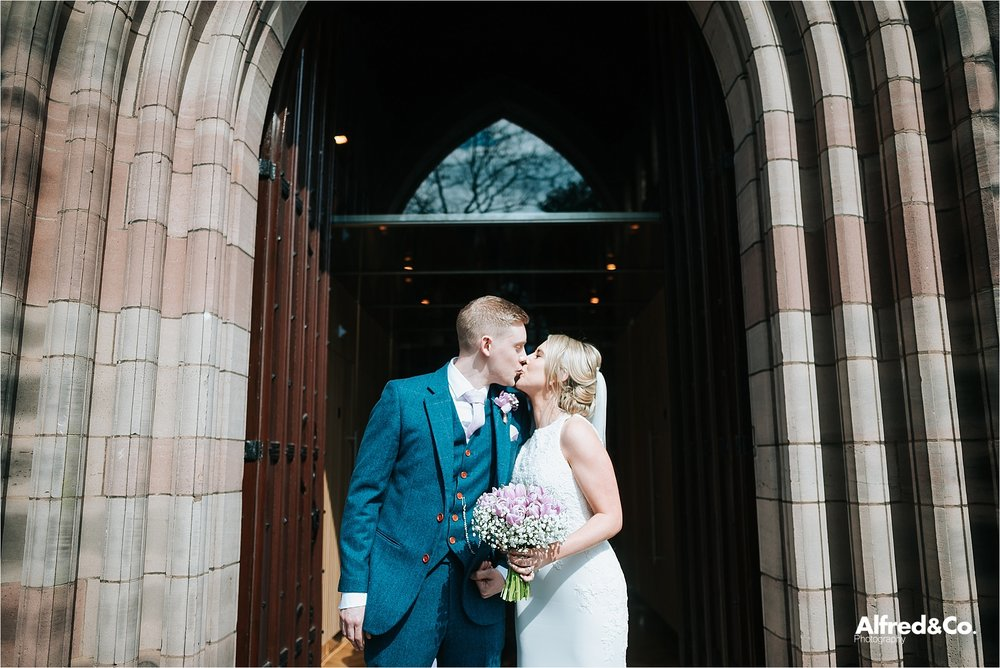 bride and groom kiss outside mossley hill church