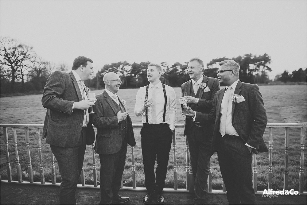 groomsmen enjoying a drink at wedding