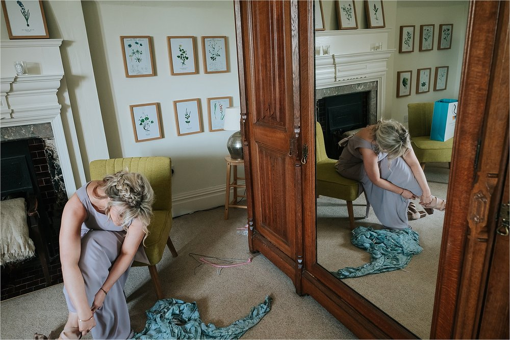 bridesmaid puts her shoes on before wedding