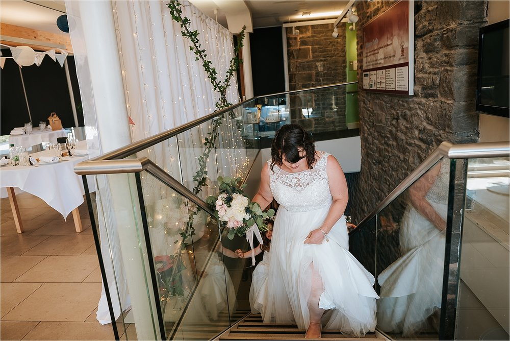 Bride walks up stairs inside The Atrium at Clitheroe Castle