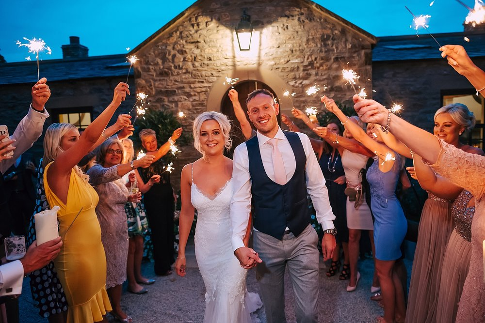 wedding couple do sparkler walk at fig house
