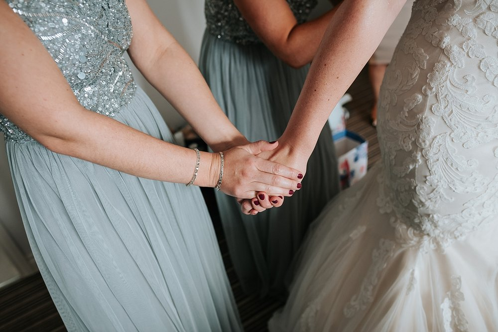 bridesmaids holds brides hand before wedding