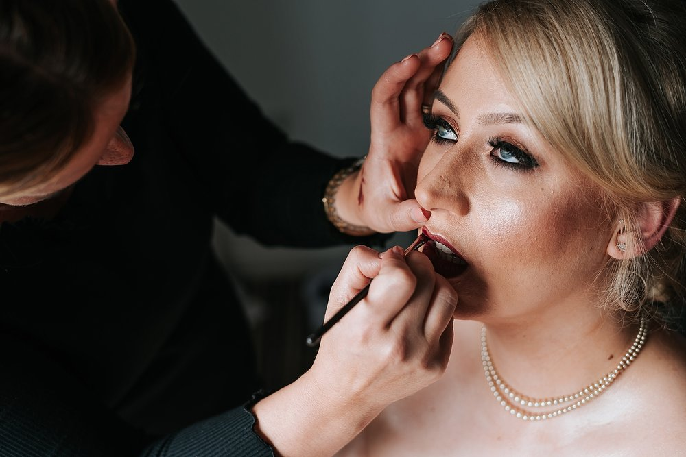 beautiful bride having make up done before wedding